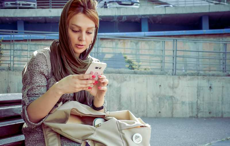 Woman with scarf on her head sitting on a bench and texting on her phone
