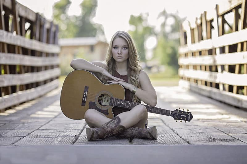 woman-sitting-while-holding-classical-guitar sitting on a wooden bridge