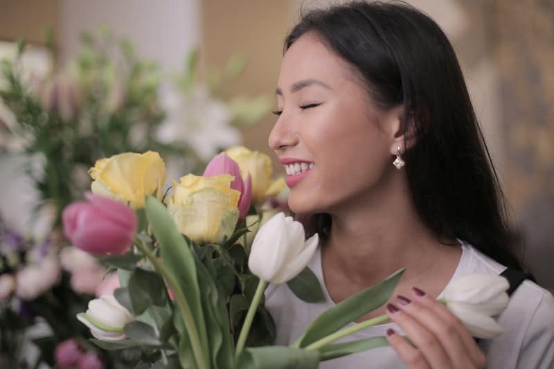 woman smelling flowers of different colors while closing her eyes