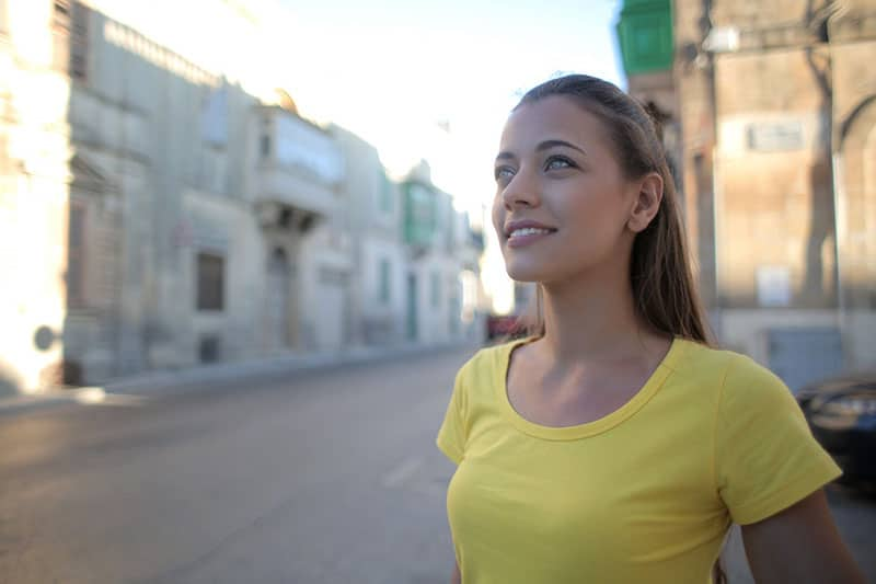 woman in yellow tshirt smiling head up
