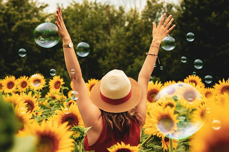 back of a woman surrounded with sunflowers and bubbles