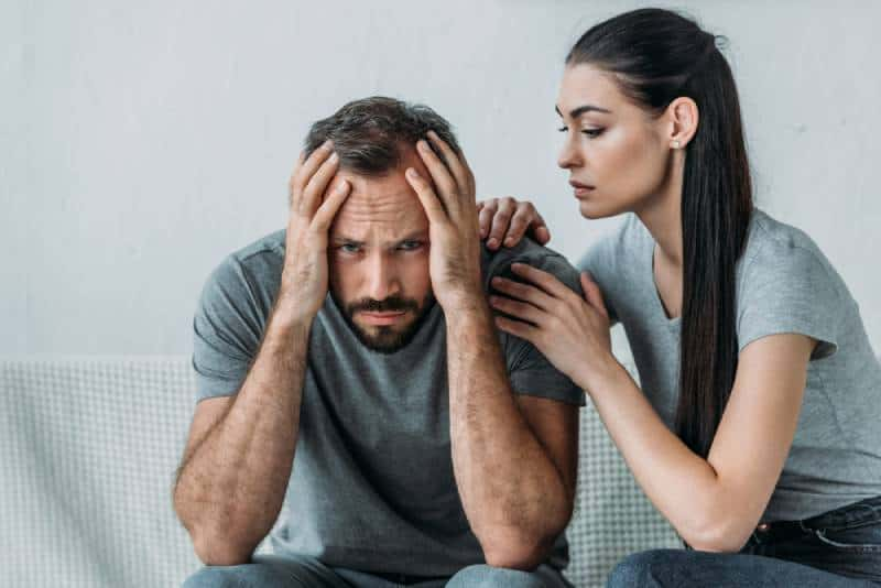 woman trying to calm her boyfriend at home