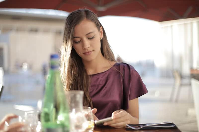 woman on purple top using smartphone