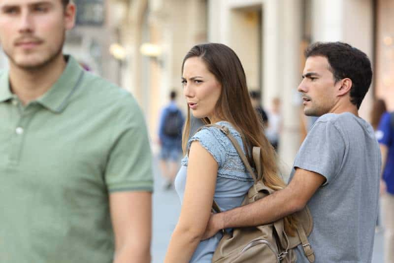 woman walking with friend and looking back at guy on sreet