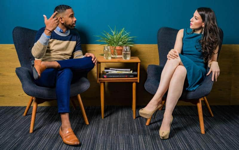 Woman wearing teal dress sitting on chair and talking to a man
