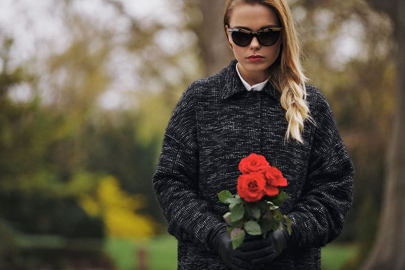 woman with glasses holding the roses