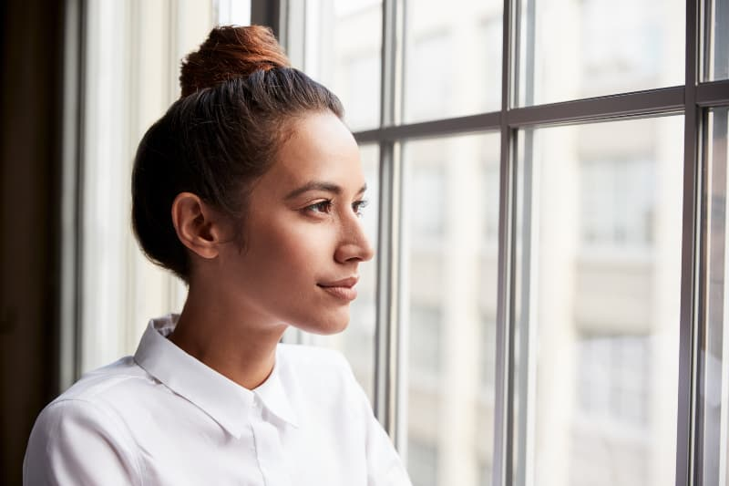 woman with hair bun looking out of window