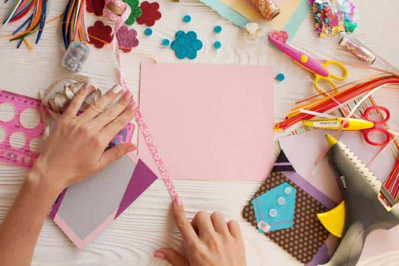 woman's hands making scrapbook with paper