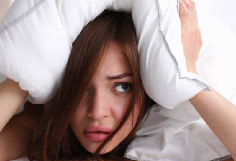 worried woman holding her head with pillow