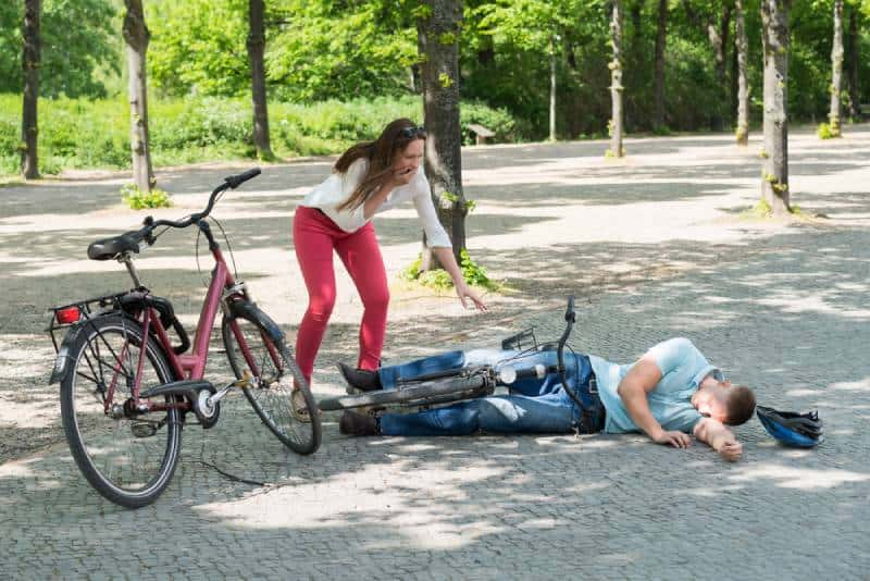 worried woman looking at man falling down while diring bicycle