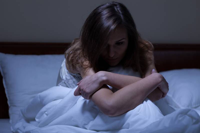 worried woman sitting on a bed