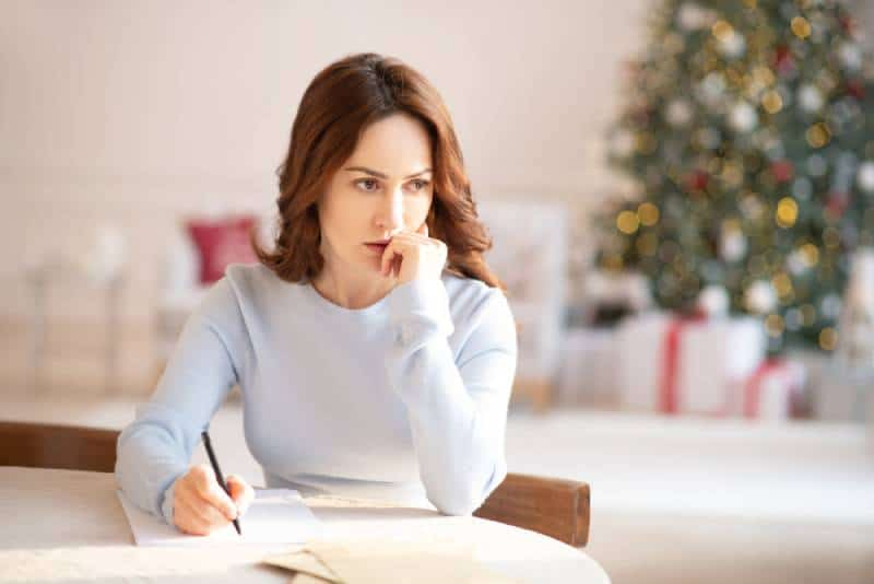 worried woman watching away while writing letter