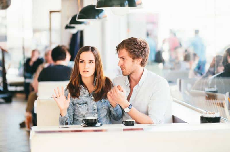 young couple flirting at bar while woman doesnt like it
