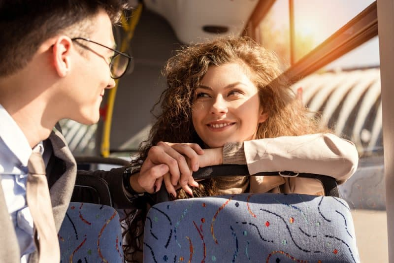 young couple riding in public transport and looking at each other