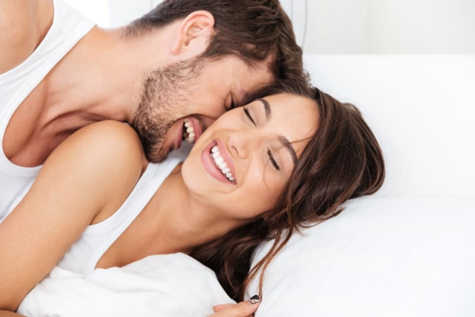young couple smiling on bed