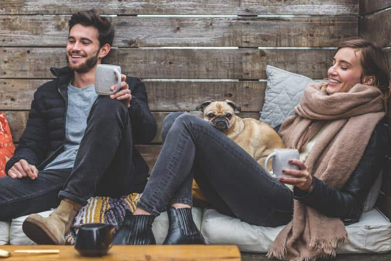 Young smiling couple with dog and tea cups sitting on a mattress by a wood wall