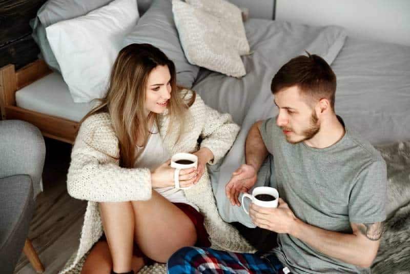 young couple talking in bedroom with coffe