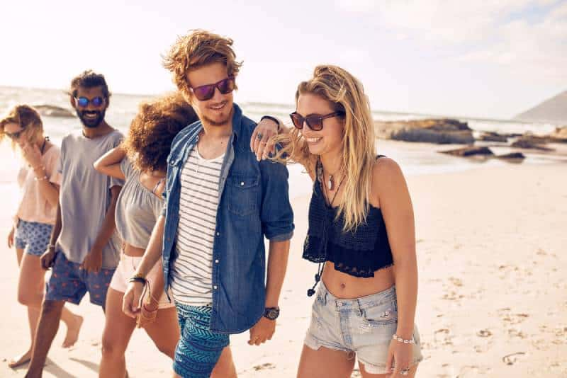 young friends walking on the beach