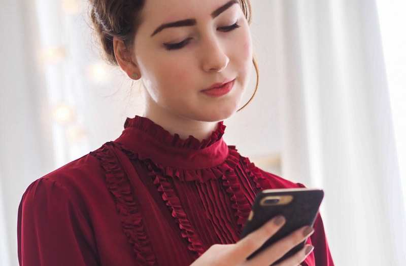 Young woman in red dress texting on a phone
