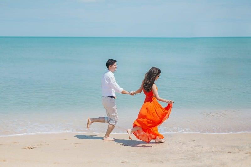 man and woman in orange dress walking beside sea