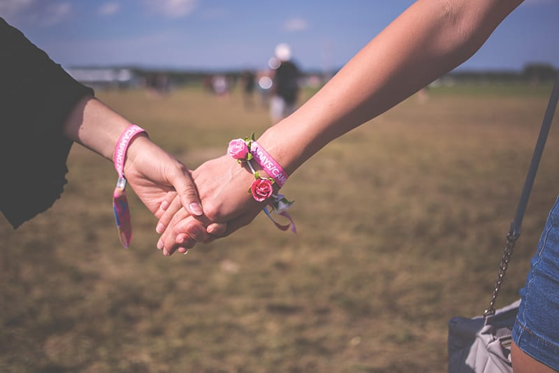 two person holding each other wearing pink friendship bracelet
