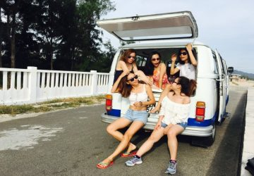 five women sitting in back of van