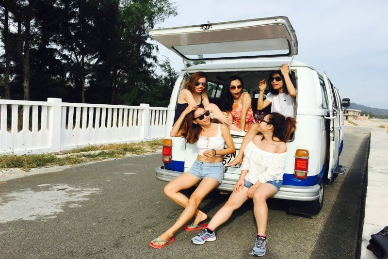 five women sitting in back of van