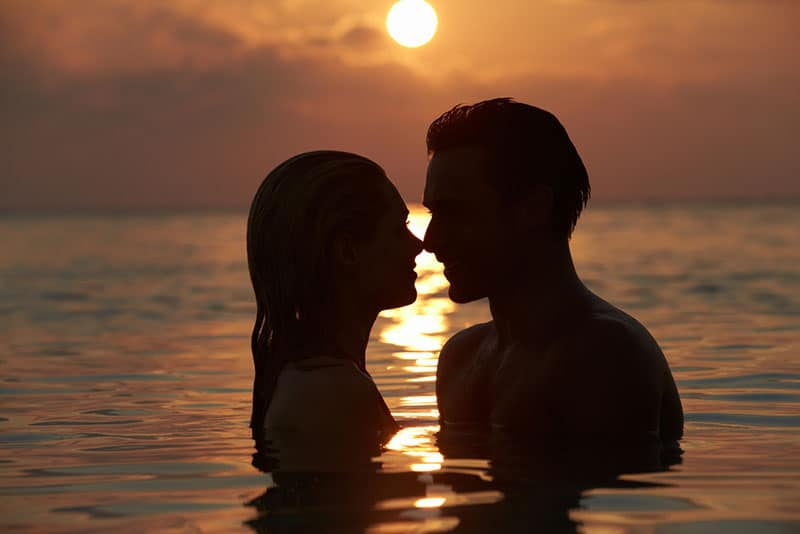 couple in the sea at sunset