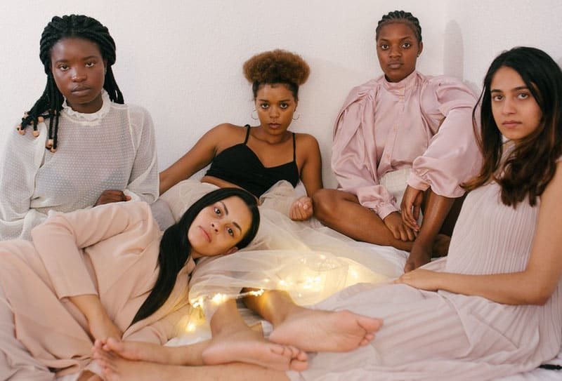 5 women sitting and lying in bed looking sad