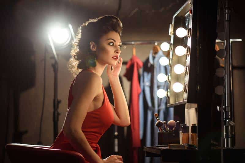 An attractive young woman prepares in a dressing room
