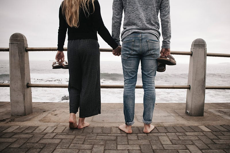 Backview of a couple's legs standing on wooden deck on sea