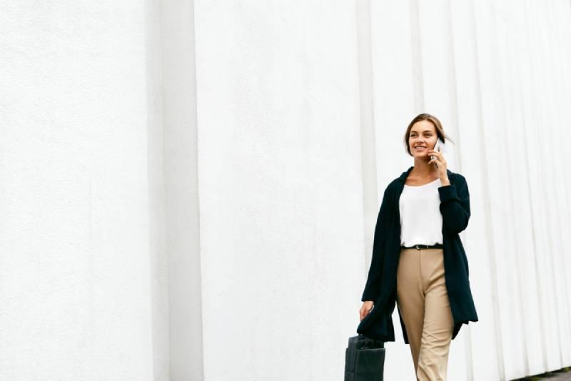 Beautiful woman talking on the phone while walking on street