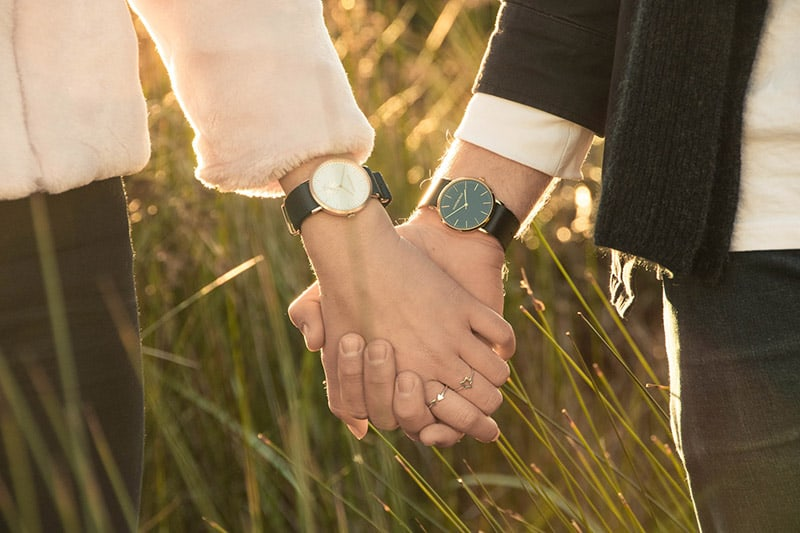 Close up of man woman's clasped hands wearing matching wristwatches