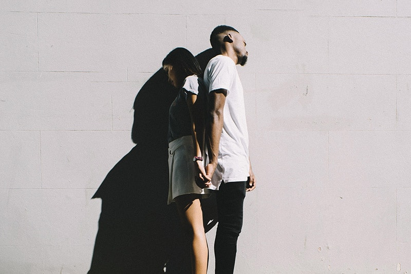 Couple standing with backs touching and holding hands