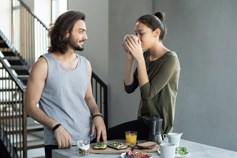 Couple eating breakfast woman drinking coffee while seated on the table