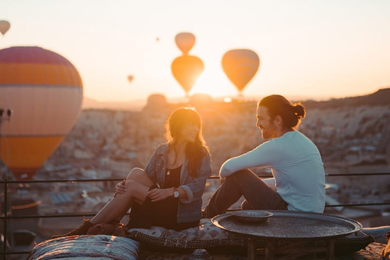Couple on a date at the rooftop viewing hot air balloons