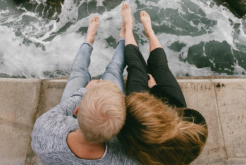 Couple sitting on dock with feet out above seawaves