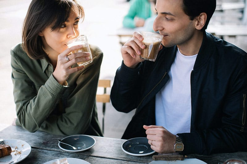 Couple drinking coffee while gazing at each other