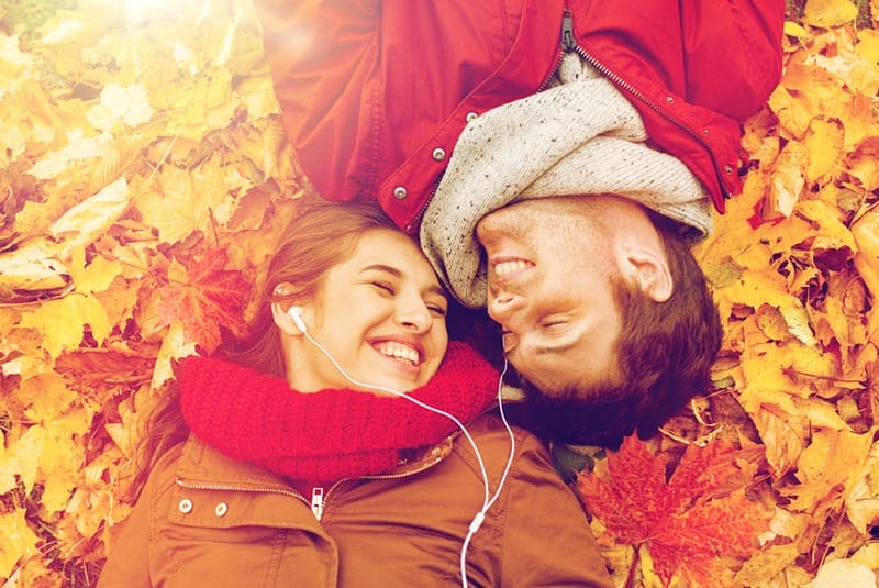 Couple sharing earphones while lying down on bed of autumn leaves