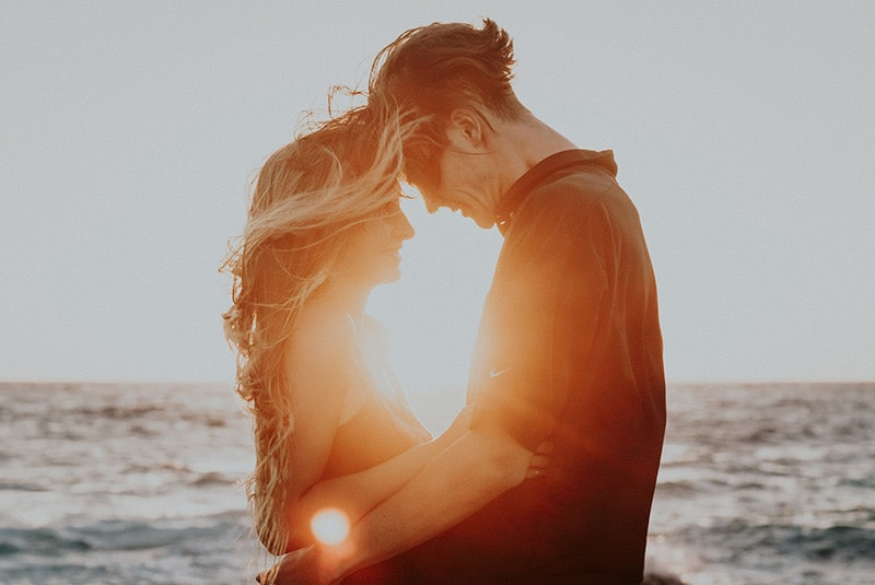 Embracing couple foreheads touching during sunset in front of the sea
