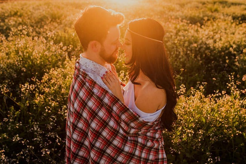 Couple in a hug covered with plaid blanket