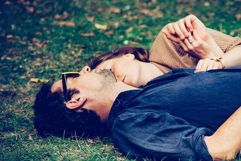 Couple hugging and lying on the grass