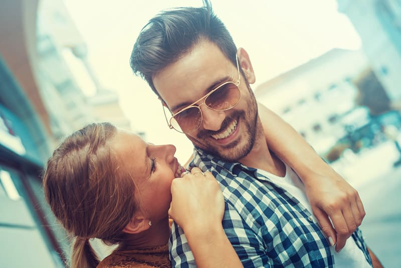 Smiling couple woman hugging man with sunglasses