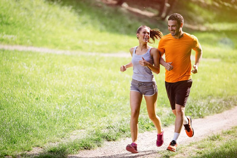 Smiling couple jogging at the park