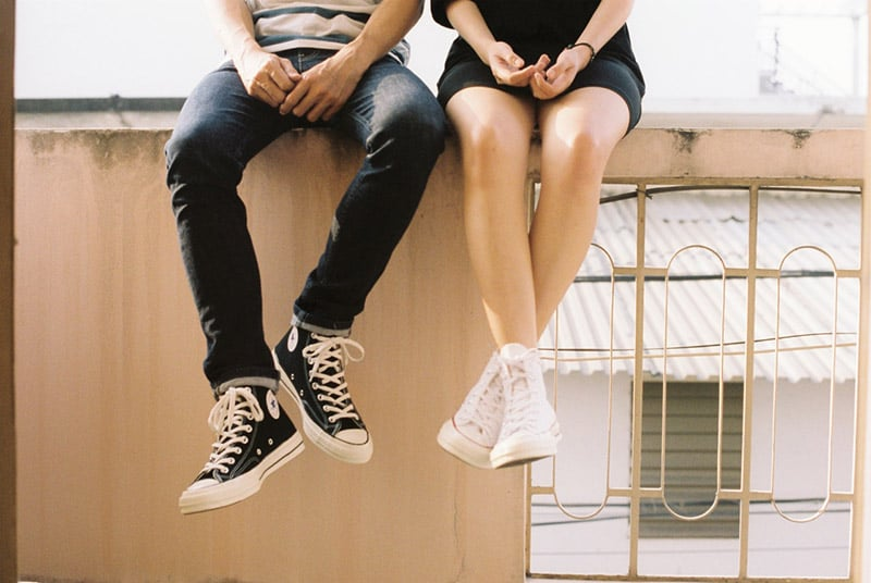 Couple sitting on balcony ledge legs shown