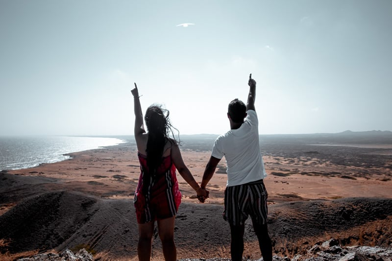 Couple holding hands other hands pointing to the sky