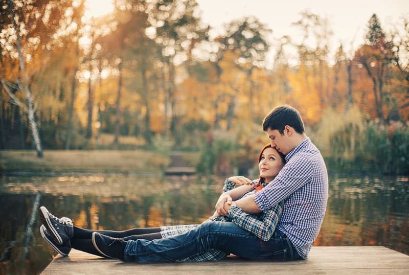 Romantic couple relaxing on the riverdock during autumn