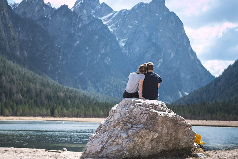 Couple sitting on rock near body of water