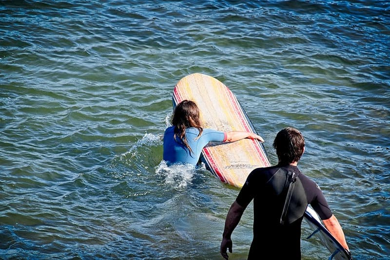 Couple surfing woman going out to open sea