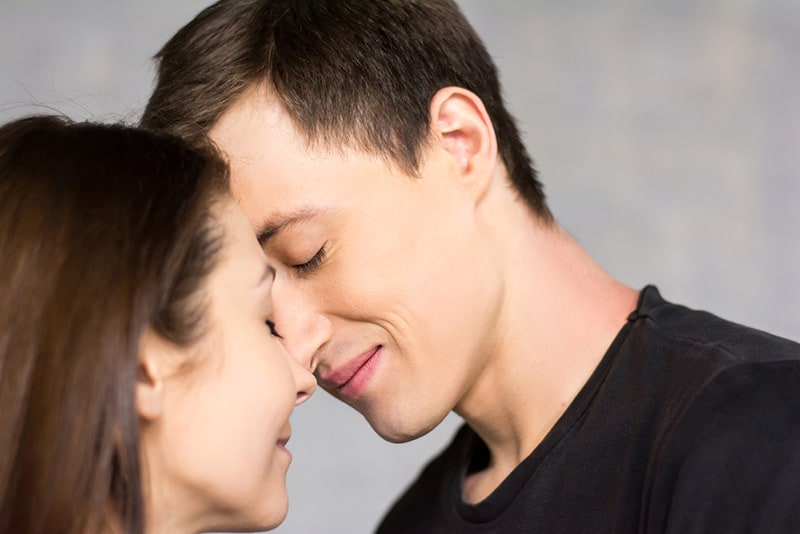 Smiling couple touching foreheads with eyes closed